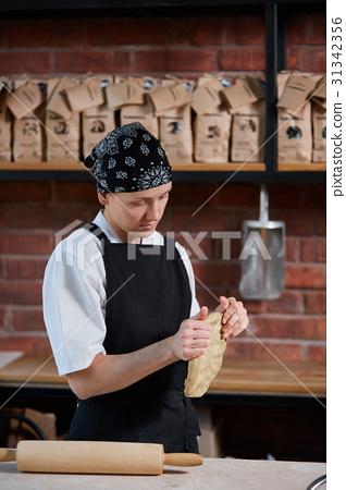 Woman kneading dough in kitchen 31342356