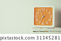 Orange wall clock on book with copy space 31345281