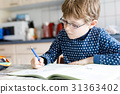 preschool kid boy at home making homework writing 31363402
