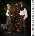 Carnival couple posing over Christmas tree 31369689