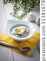 Sorrel soup with egg in white bowl. 31381678