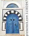 Arched Doorway with Blue Studded Door 31383947