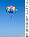 Skydiver on colorful parachute in sunny blue sky 31384021