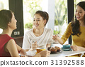 Girlfriends are eating and talking together at the coffee shop. 31392588