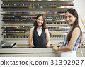 A photo of two women smiling and standing at nail salon counter 31392927