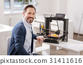 Handsome delighted man sitting near the 3d printer 31411616