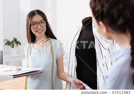 Smiling brunette tailor holding a tail of cardigan 31412985