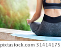 young woman meditating while sitting in lotus pose 31414175