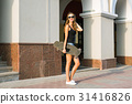 Beautiful young woman in sunglasses with skate 31416826