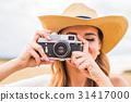 Woman holding retro camera close-up 31417000