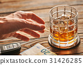 Man's hand reaching to glass with alcohol drink  31426285