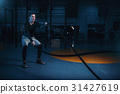 Sportsman on training, workout with battle ropes 31427619