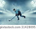 Ice hockey player in equipment poses on stadium 31428095
