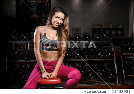Girl execute exercise with dumbbells . 31432991