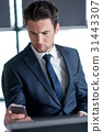 Stylish young man in suit is reading information 31443307