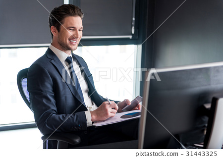 Joyful young man is working in office 31443325