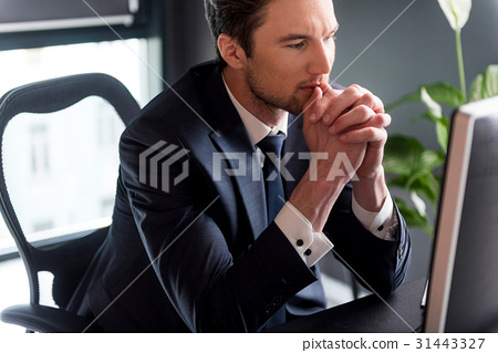 Elegant pensive man is working with concentration 31443327