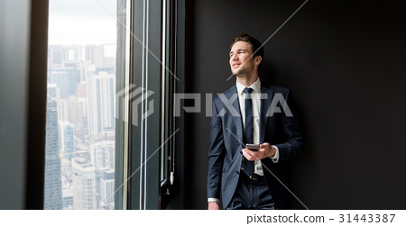 Cheerful pleasant businessman is standing in 31443387