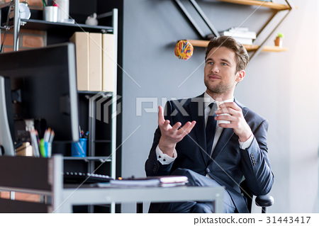 Pleasant positive employee is relaxing in office 31443417