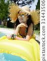 Beautiful woman in sun hat sunbathing on air mattress in the swi 31443506