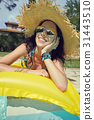 Beautiful woman in sun hat sunbathing on air mattress in the swi 31443510