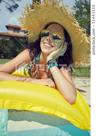 Beautiful woman in sun hat sunbathing on air mattress in the swi 31443510