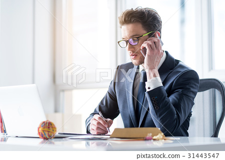 Energetic young man is sitting in office 31443547
