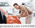 Cheerful male looking at car in room 31443988