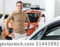 Cheerful man standing in automobile showroom 31443992