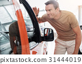 Happy male watching car interior in showroom 31444019