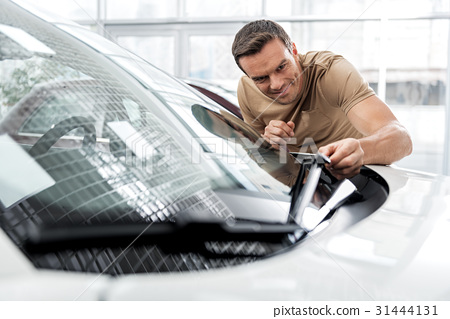Outgoing man standing near automobile 31444131