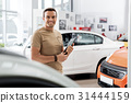 Outgoing man holding automobile documents in hands 31444159