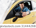 Happy male correcting side mirror in car 31444268