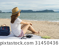 Female Traveler sitting on beach 31450436