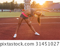 Fit woman warming up in stadium, bending and 31451027