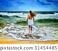 Summer girl sea. Woman goes at water on coast. 31454485