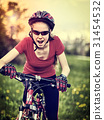 Woman traveling bicycle on green grass in summer 31454532