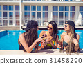 cheerful girls drinking cocktails in the pool 31458290