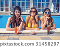 cheerful girls drinking cocktails in the pool 31458297
