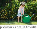 cute little boy with water can in garden 31465484