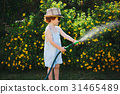 little boy watering the garden with hose 31465489
