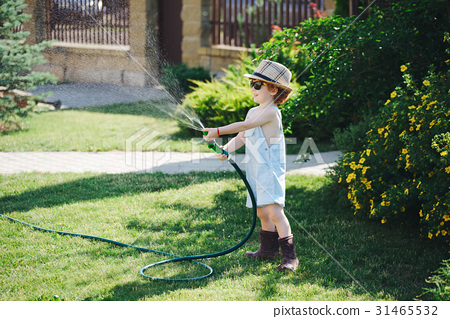 little boy watering the garden with hose 31465532