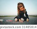 little girl draws pictures on asphalt 31465814