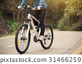 Young woman riding mountain bike on forest trail 31466259