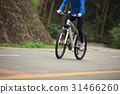 Young woman riding mountain bike on forest trail 31466260