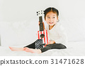 Asian little girl playing ukulele in bedroom 31471628