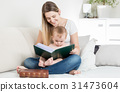 mother reading story to her 9 months old baby boy 31473604