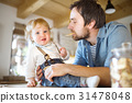 Young father at home with his little son eating 31478048