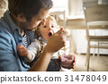 Young father at home feeding his little son with 31478049