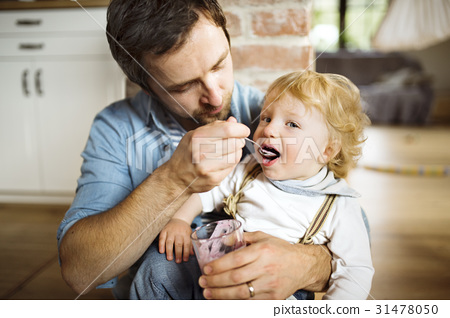 Young father at home feeding his little son with 31478050